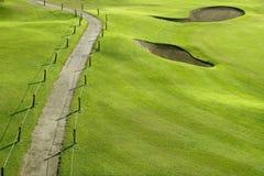 Hügelfeld des grünen Grases des Golfplatzes mit Löchern Stockfotos