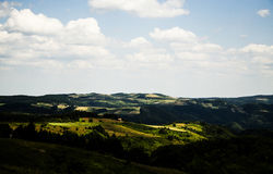 Hügelige Landschaft sonnenbeschien Stockfotografie