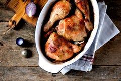 Hühnerbeine backten mit frischem Rosmarin und Pfeffer auf einem alten hölzernen Hintergrund Rustikale Art stockbilder