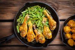 Hühnerbeine in der Wanne mit Kartoffeln und Salat Lizenzfreie Stockfotos