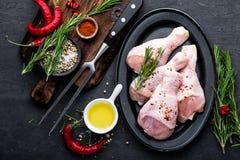 Hühnerbeine, Trommelstöcke und Bestandteile für das Kochen, rohes Fleisch auf schwarzem Hintergrund lizenzfreies stockfoto