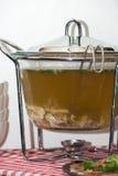 Hühnerbrühe in einem transparenten Glastopf lizenzfreie stockfotos