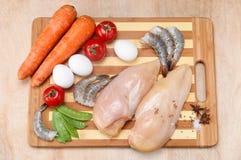 Hühnerbrustfleisch und -garnelen auf hölzernem Brett Stockbilder