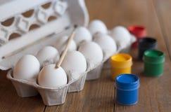 Hühnereien in einem Behälter und bunte Farbe Lizenzfreies Stockbild