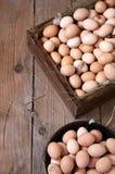 Hühnereien in einer Holzkiste und in einem runden Behälter Stockfoto