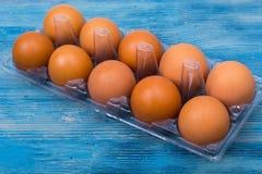 Hühnereien mit farbigem Oberteil im Plastikkasten Stockfotos