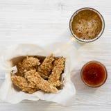Hühnerfinger mit sauer-süßer Soße und kaltem Bier auf einem weißen Holztisch, Draufsicht Obenliegend, von oben, flache Lage lizenzfreie stockbilder