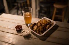 Hühnerflügel, Bier, Soßen auf dem Tisch in der Kneipe Stockfoto