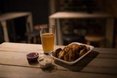 Hühnerflügel, Bier, Soßen auf dem Tisch in der Kneipe Stockfotos