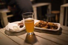 Hühnerflügel, Bier, Soßen auf dem Tisch in der Kneipe Stockfotografie