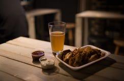 Hühnerflügel, Bier, Soßen auf dem Tisch in der Kneipe Lizenzfreies Stockbild