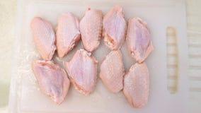 Hühnerflügel, die auf einen weißen Block schneiden Stockbild