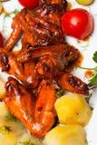 Hühnerflügel grillten mit gekochten Kartoffeln und legten Tomaten in Essig ein Lizenzfreie Stockfotografie