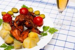 Hühnerflügel grillten mit gekochten Kartoffeln und marinierten Tomaten Lizenzfreies Stockfoto