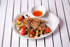 Hühnerflügel mit grünen Bohnen, Hülsen Mais, Kirschtomaten Stockbild