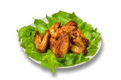 Hühnerflügel mit Salat verlässt auf einem weißen Hintergrund Lizenzfreies Stockfoto