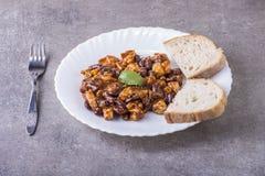 Hühnerfleisch mit Bohnen sauce mit Brot auf der Platte auf Weiß lizenzfreie stockfotos
