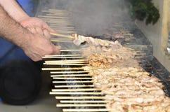Hühnerkebabs auf dem Grill und den menschlichen Händen Lizenzfreies Stockbild