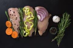 Hühnerleistenleiste mit Rosmarin und Gemüse, Karotten Pfeffer, Knoblauchzwiebeln Lizenzfreies Stockbild