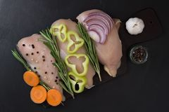 Hühnerleistenleiste mit Rosmarin und Gemüse, Karotten Pfeffer, Knoblauchzwiebeln Stockbild