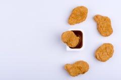 Hühnernugget, das in der roten Badsoße, umgeben durch MOR vier steht Stockfoto