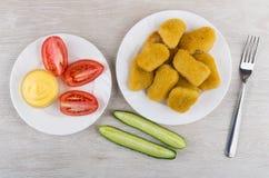 Hühnernuggets in der Platte, in den Tomaten, in den Gurken, in der Majonäse und in FO Stockbild