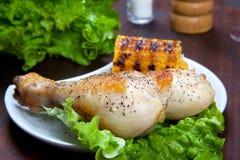 Hühnerschenkel mit einer Grenze des Maiskolbens und des Salats Lizenzfreie Stockfotografie