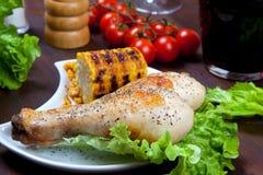 Hühnerschenkel mit einer Grenze des Maiskolbens und des Salats Lizenzfreie Stockfotos