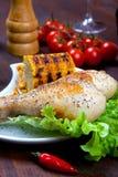Hühnerschenkel mit einer Grenze des Maiskolbens und des Salats Stockfoto
