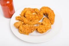 Hühnerstreifen auf weißer Platte mit scharfer Soße auf Seite Lizenzfreies Stockbild