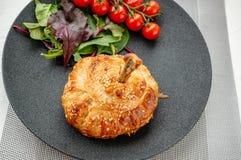 Hühnertrommelstock im Teig gebacken im Ofen mit Kartoffeln, Tomaten, Zwiebeln und Gewürzen mit einer Beilage von Tomaten und von  stockfotos