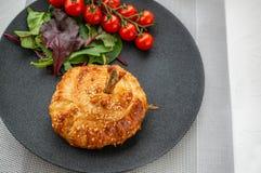Hühnertrommelstock im Teig gebacken im Ofen mit Kartoffeln, Tomaten, Zwiebeln und Gewürzen mit einer Beilage von Tomaten und von  stockbilder
