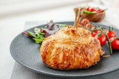 Hühnertrommelstock im Teig gebacken im Ofen mit Kartoffeln, Tomaten, Zwiebeln und Gewürzen mit einer Beilage von Tomaten und von  stockfoto