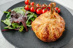Hühnertrommelstock im Teig gebacken im Ofen mit Kartoffeln, Tomaten, Zwiebeln und Gewürzen mit einer Beilage von Tomaten und von  lizenzfreie stockbilder