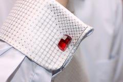 Hülse eines weißen Hemdes mit einem roten Manschettelink Lizenzfreie Stockfotografie