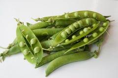 Hülsen von grünen Erbsen auf einem weißen Hintergrund Stockbild