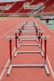 Hürden auf roter Laufbahn im Stadion stockbilder