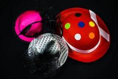 Hüte auf schwarzem Hintergrund, Karnevalshüte, Parteihüte lizenzfreie stockbilder