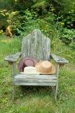 Hüte auf Stuhl draußen Lizenzfreies Stockfoto