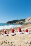 Hüte von Santa Claus am Strand lizenzfreie stockbilder