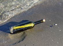 Hüten Sie Karte in der Flasche auf dem Ufer des Ozeans Lizenzfreies Stockbild