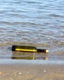 Hüten Sie Karte in der Flasche auf dem Ufer des Ozeans Stockfotos