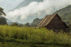 Hütte im nebeligen Waldtal Lizenzfreie Stockbilder