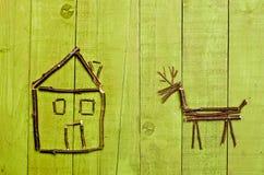 Hütte und Ren vereinbarten von den Stöcken auf hölzernem grünem backgraund Stockfoto