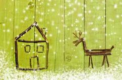 Hütte und Ren vereinbarten von den Stöcken auf hölzernem grünem Hintergrund Stockfotos