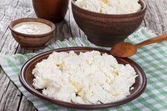 Hüttenkäse auf Teller mit Löffel und Creme in der Schüssel Lizenzfreies Stockbild