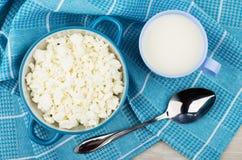 Hüttenkäse in der blauen Schüssel, in der Schale Milch und im Löffel Lizenzfreie Stockbilder