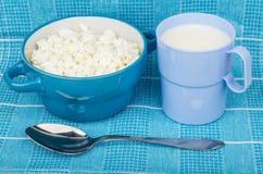 Hüttenkäse in der Schüssel, in der Schale Milch und im metallischen Löffel Lizenzfreies Stockbild