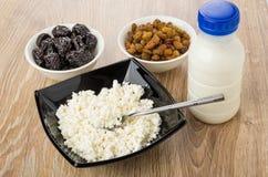 Hüttenkäse, Teelöffel in der Schüssel, Jogurt, Rosinen und Pflaumen Stockfotos