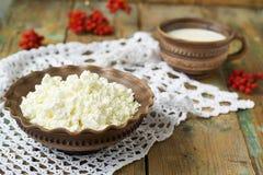 Hüttenkäse und Milch in einem Tongefäß Stockfotos